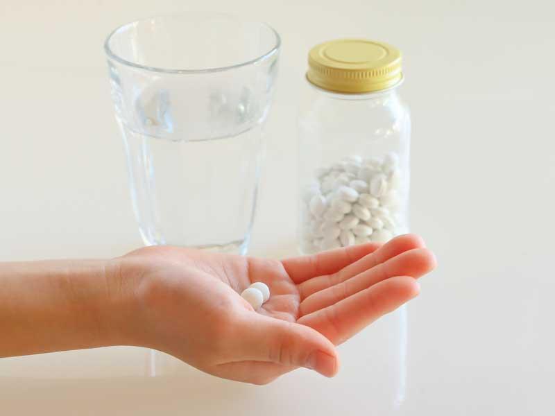 薬を持つ子供の手