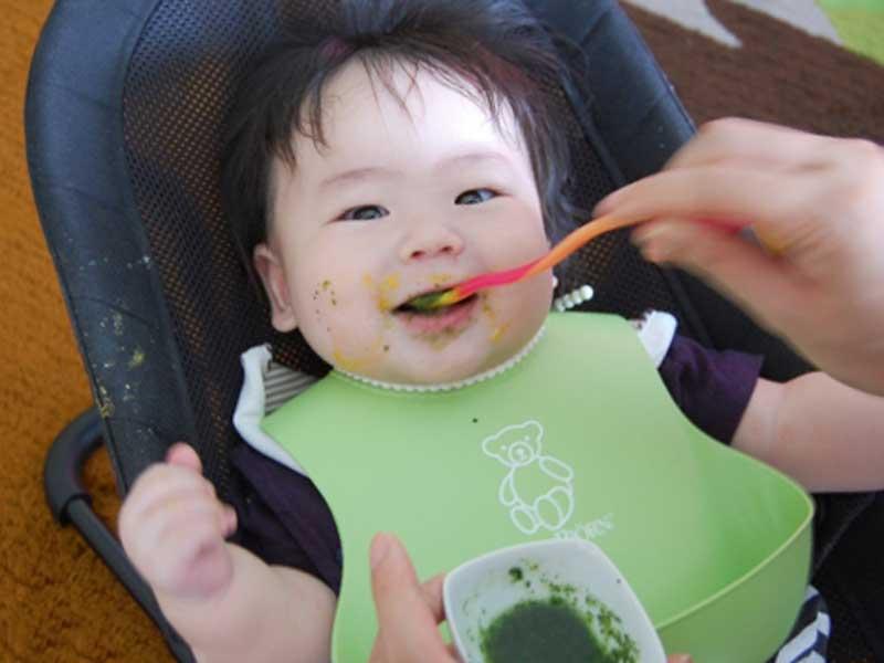 笑顔で離乳食を食べる赤ちゃん