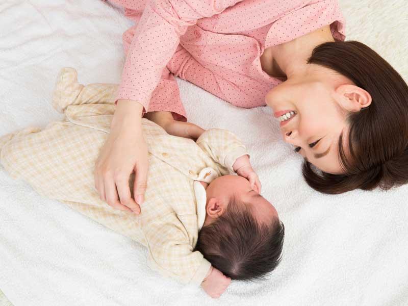 寝転がるお母さんと赤ちゃん