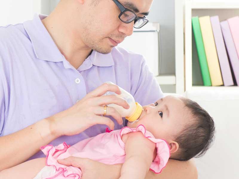 赤ちゃんにミルクを飲ませるパパ