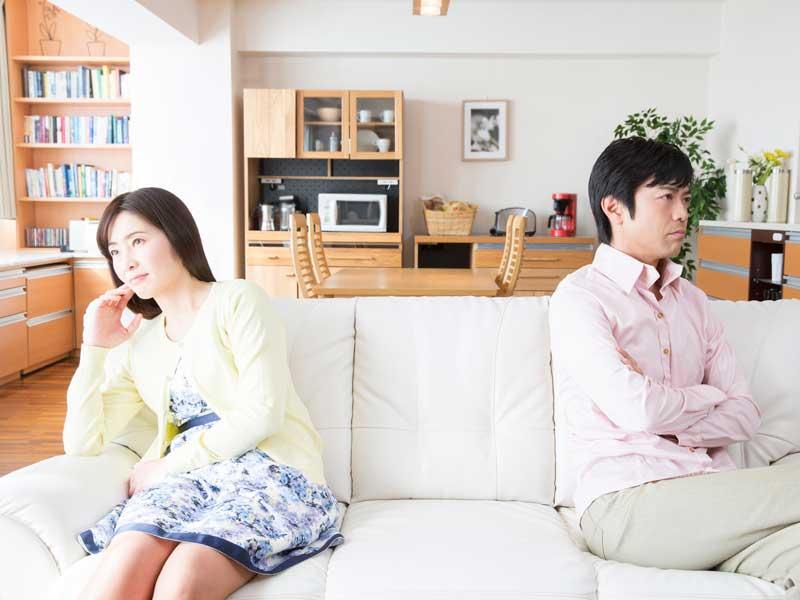 喧嘩して1つのソファーに離れて座っている夫婦