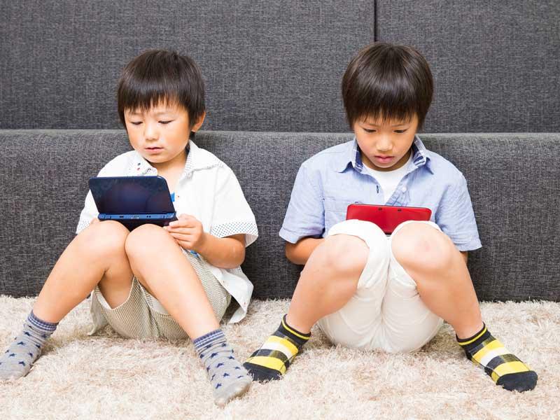 ゲーム機で遊んでいる子供達