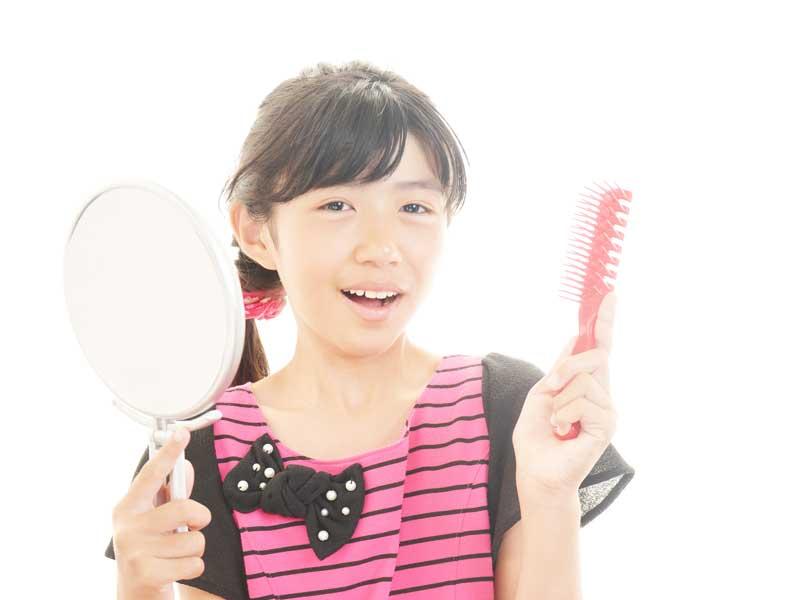 鏡とくしを持つ女の子