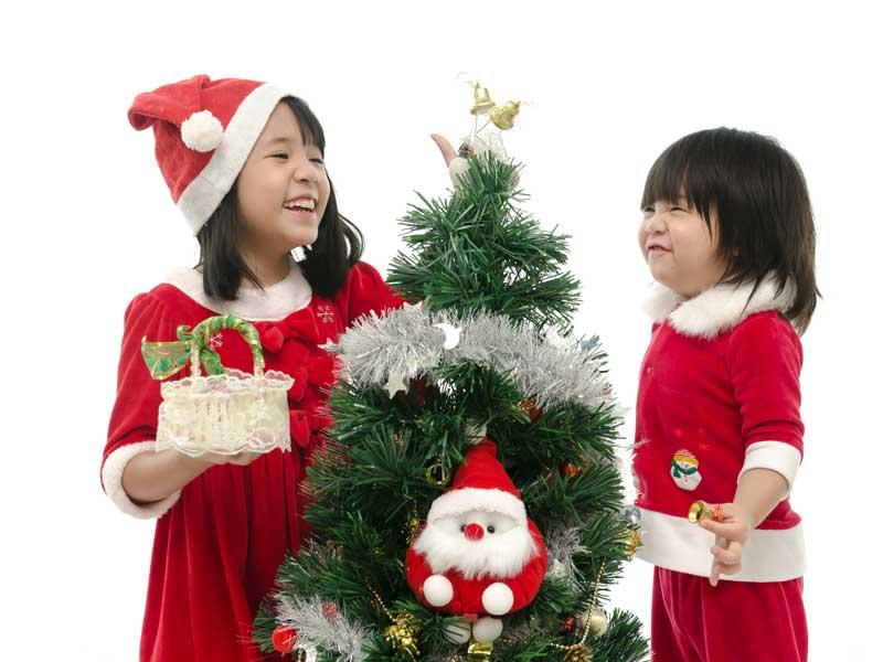 クリスマスツリーの飾りをする姉妹