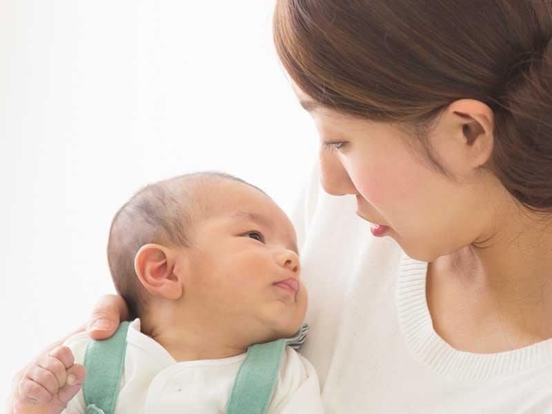 新生児を抱っこするママ