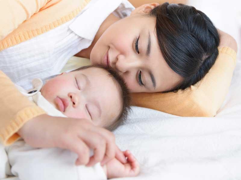 赤ちゃんと一緒に寝るお母さん