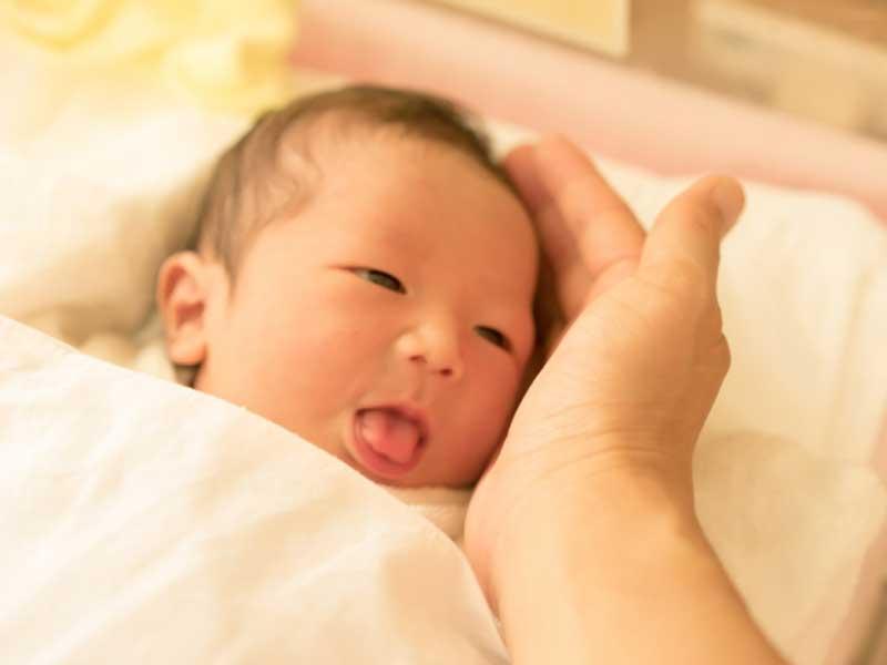 新生児を触るママの手