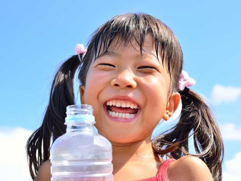 青空で水を飲む女の子