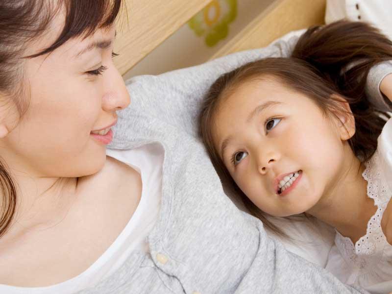 ベッドで話するママと娘