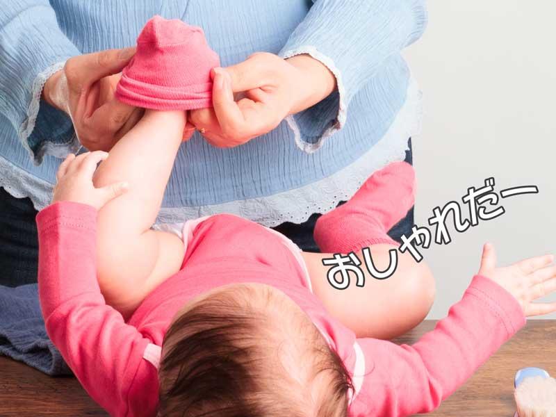 赤ちゃんに靴下を履かせるお母さん