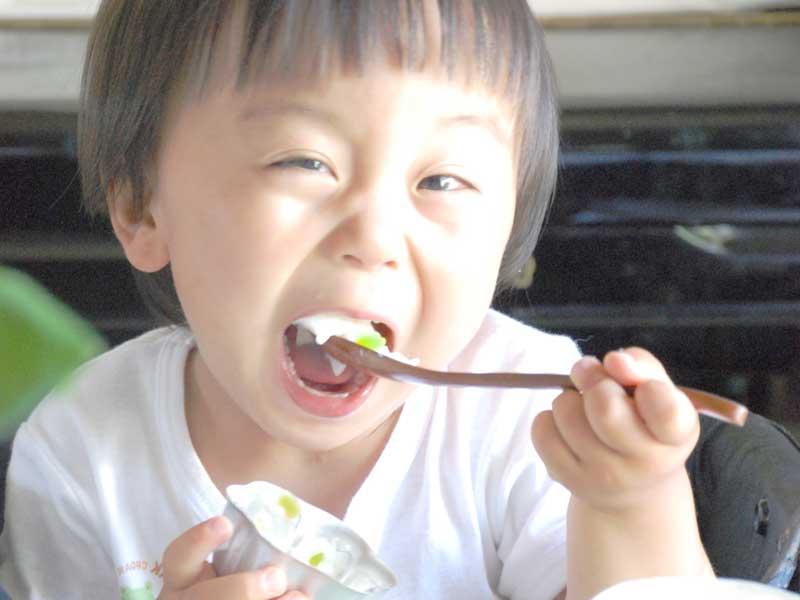 おいしそうにお粥を食べる子供