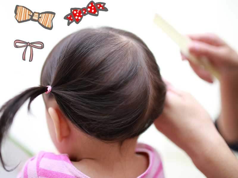 娘にヘアセットするママの手