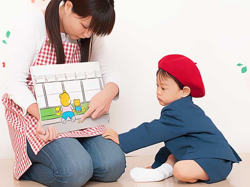 紙芝居を読む保育士と園児
