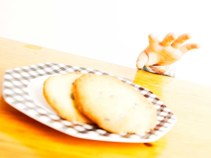 テーブルの上のクッキーを取ろうとする子供の手