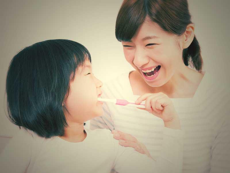 歯磨きをしている小学生とお母さん