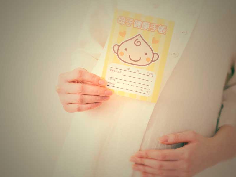 母子手帳を持つ正産期の妊婦さん