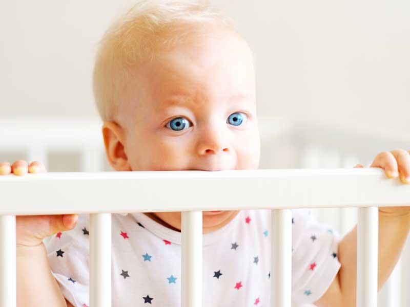 ベビーベッドをかじる赤ちゃん