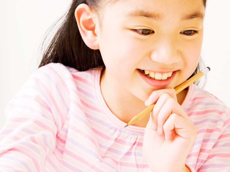 ペンを持つ笑顔の女の子