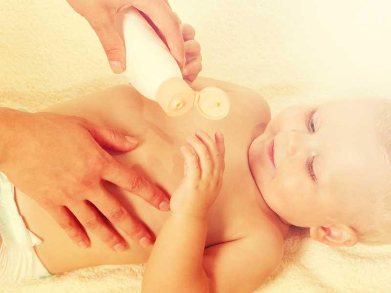赤ちゃんに保湿ケアするママの手