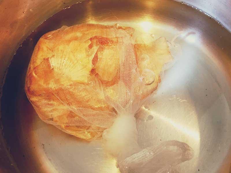 ネットに入れた玉ねぎの皮を鍋で煮てる