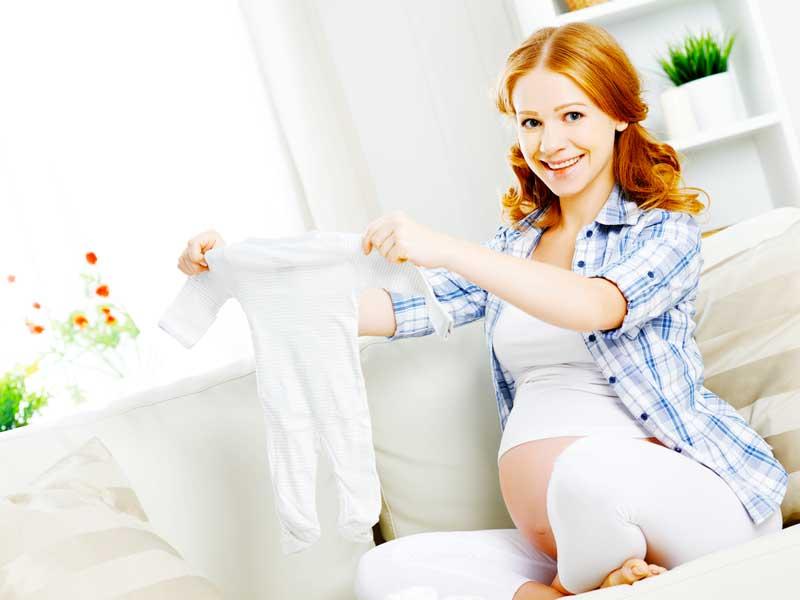 赤ちゃんの肌着を持つ妊婦さん