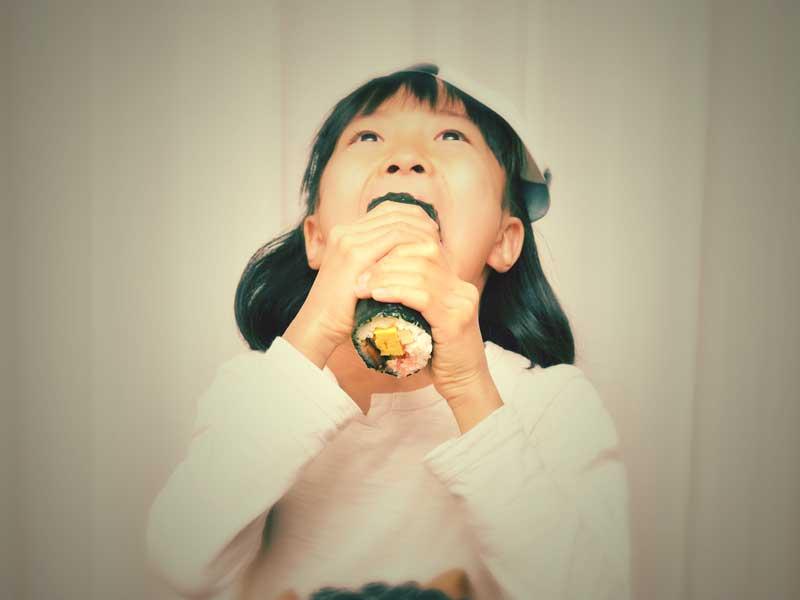 恵方巻きを食べる女の子