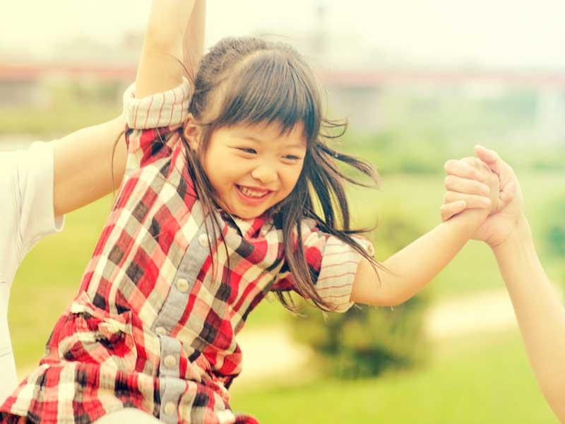親と手を繋ぐ笑顔の女の子