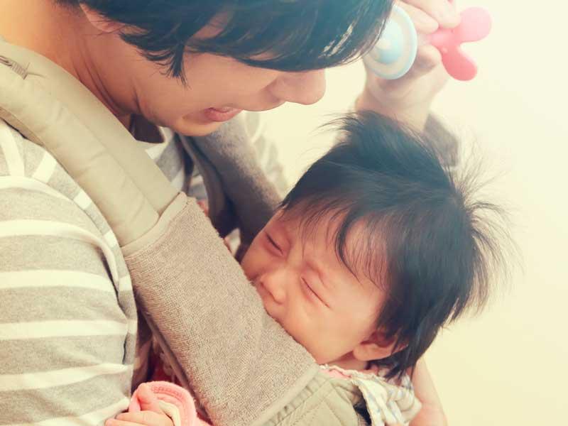 パパに抱っこされ泣いている赤ちゃん