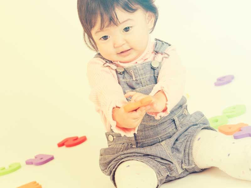 おもちゃを手渡しする赤ちゃん