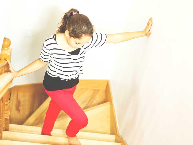 壁を触りながら歩く女の子