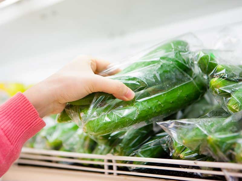 スーパーマーケットの胡瓜を持つ女性の手