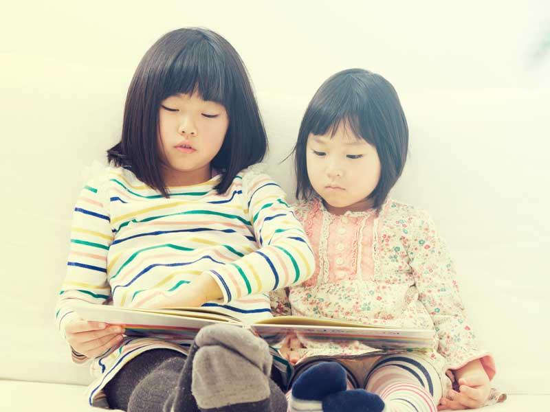 絵本を読んでいる姉妹