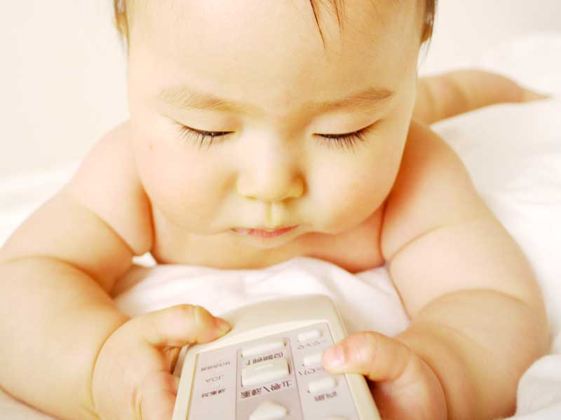 エアコンのリモコンを持つ赤ちゃん