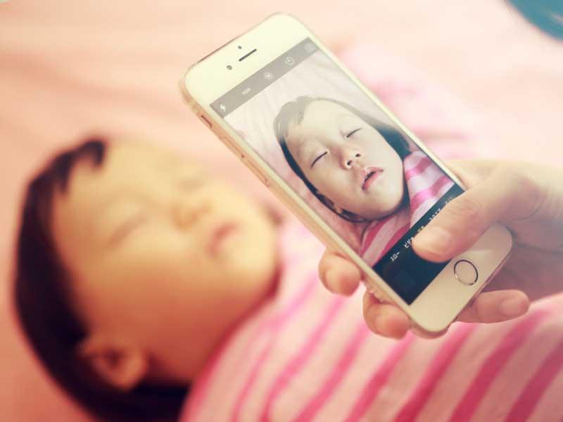 スマホで赤ちゃんの寝顔の写真を撮るママ