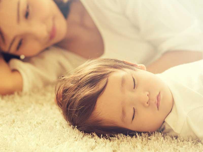 子供と添い寝をしているママ