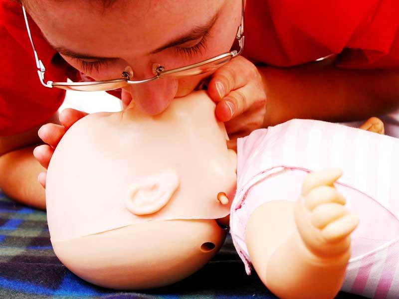 赤ちゃんへの人口呼吸の練習するママ