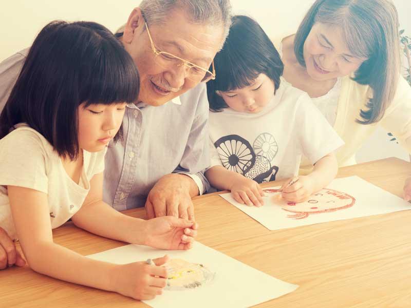 似顔絵を書く孫と祖父祖母