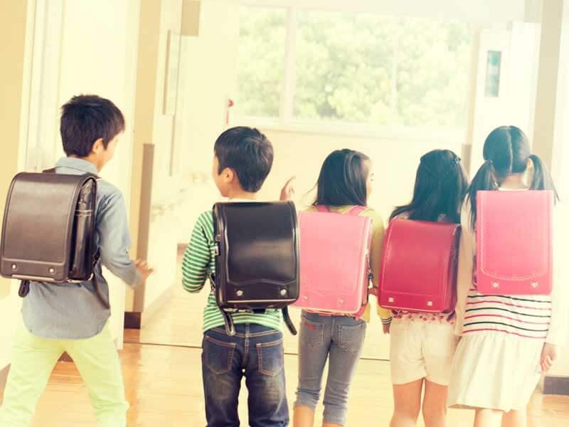 ランドセルを背負って廊下を歩く小学生達