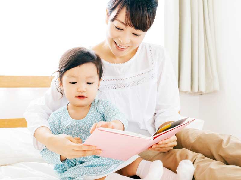 子供に絵本を読み聞かせるママ