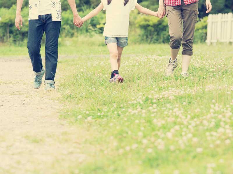 公園で手を繋いで散歩する家族