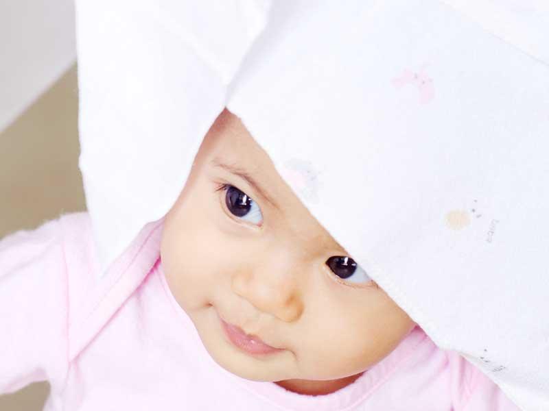 布おむつを頭にかぶってる笑顔の赤ちゃん