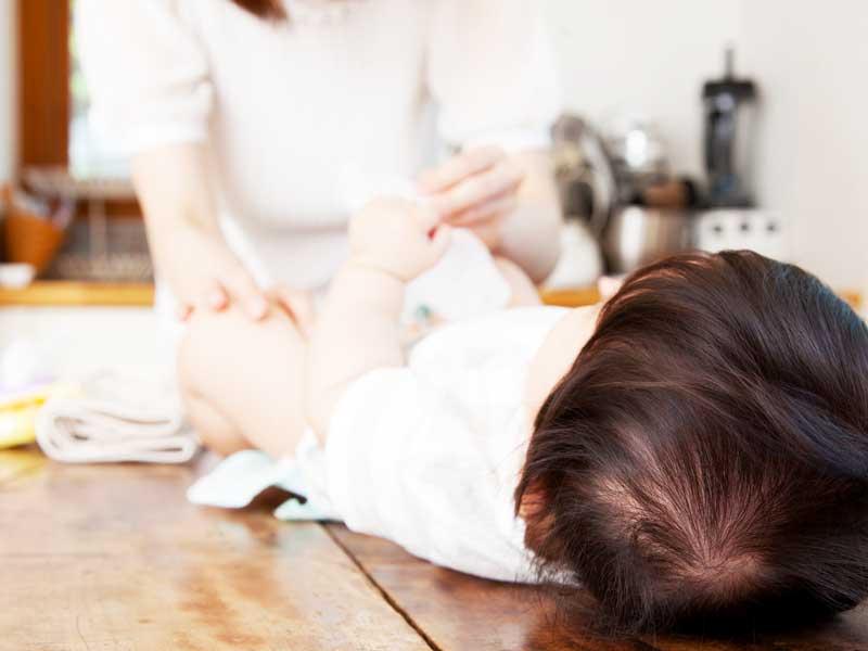 赤ちゃんのおむつ交換するママ