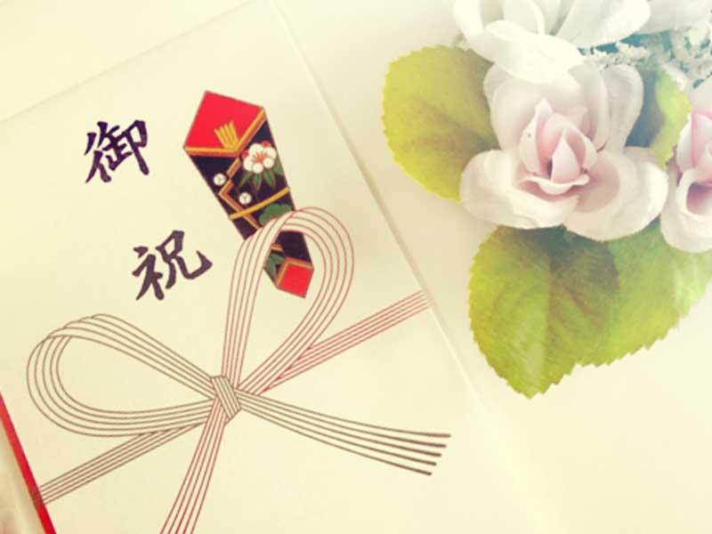 御祝の封筒と花