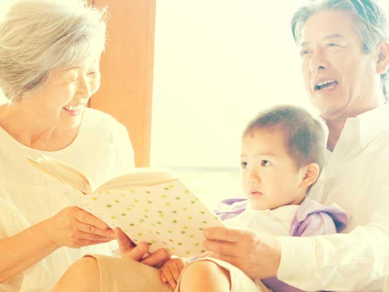 孫に絵本を読み聞かせる祖父母