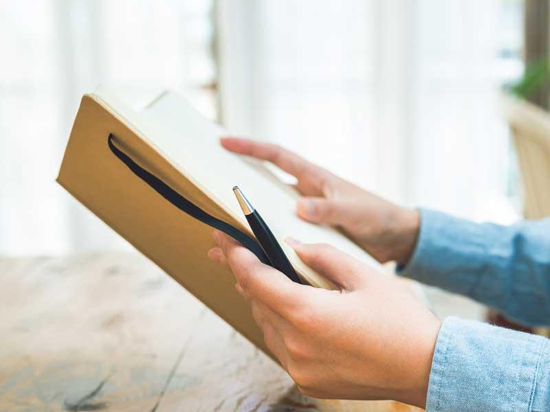 日記帳を持つママの手