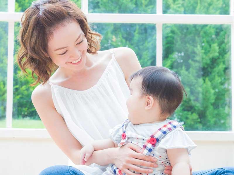 笑顔の赤ちゃんを抱っこしている母親