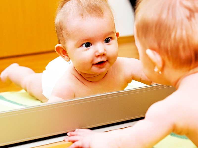 鏡の中の自分を見る赤ちゃん
