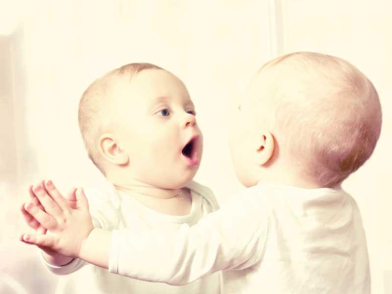 鏡の前に立つ赤ちゃん