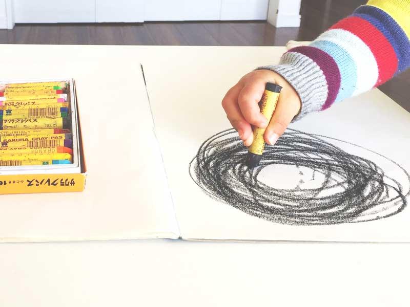グルグル丸を描く子供の手