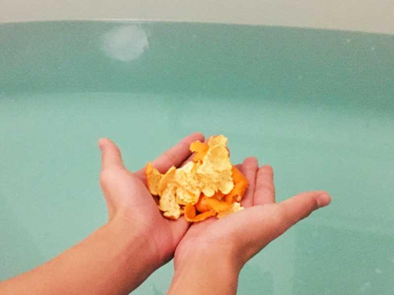 みかんの皮をお風呂の中に入れるお母さんの手